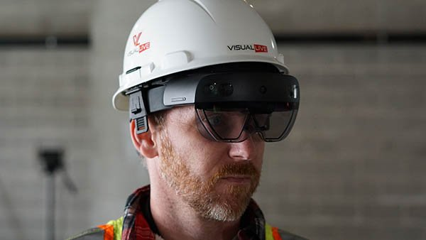 construction worker on jobsite wearing VisualLive AR with HoloLens 2 glasses flipped down